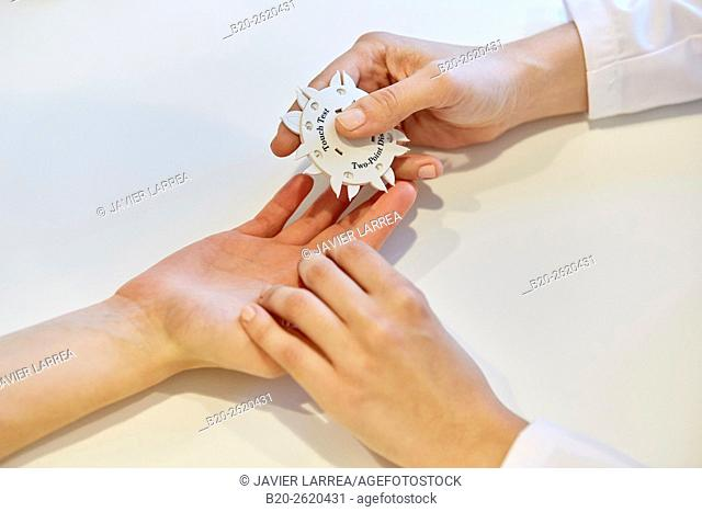 Weber test. Hand Surgery. Discrimination sensitive test used in the exploration of the peripheral nerve. Doctor attending to patient medical consultation
