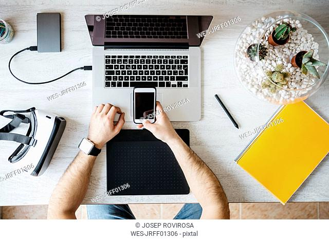 Man working with smartphone and laptop at home office, top view