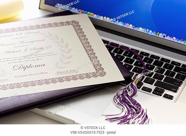 Close-up view of graduation tassel and diploma on laptop