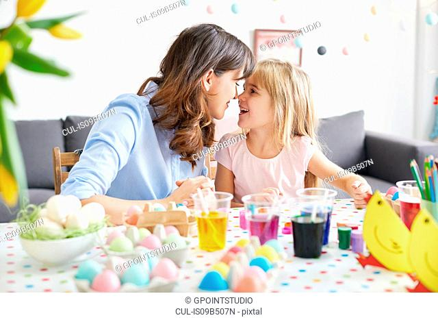 Woman and daughter nose to nose while painting easter eggs at table