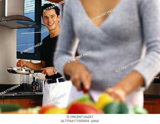In kitchen, man holding pan, woman cutting vegetables in blurred foreground