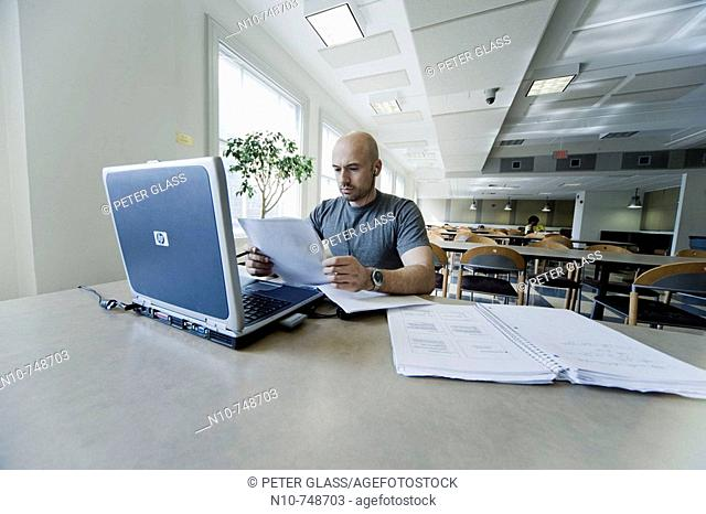 Balding young man working on his laptop computer in the dining area at his college
