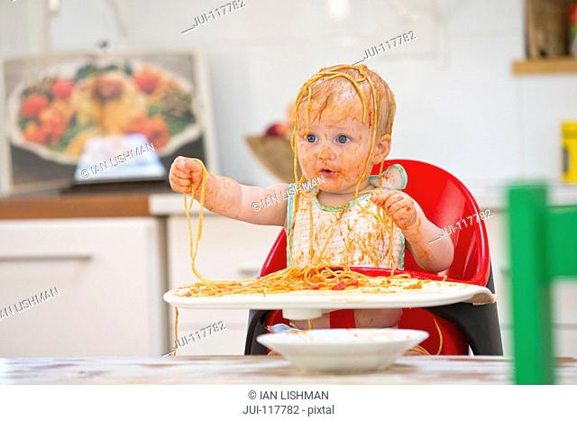 Messy Baby Boy Sits In High Chair Covered In Spaghetti And Sauce