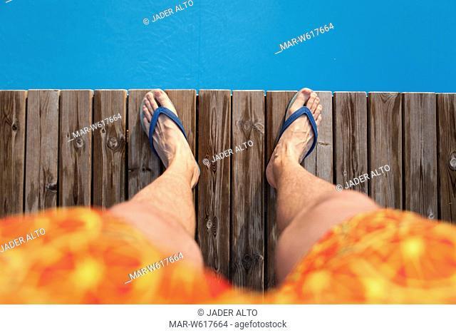 gambe di un uomo in costume sul bordo di una piscina