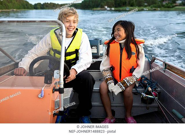 Smiling brother and sister on boat