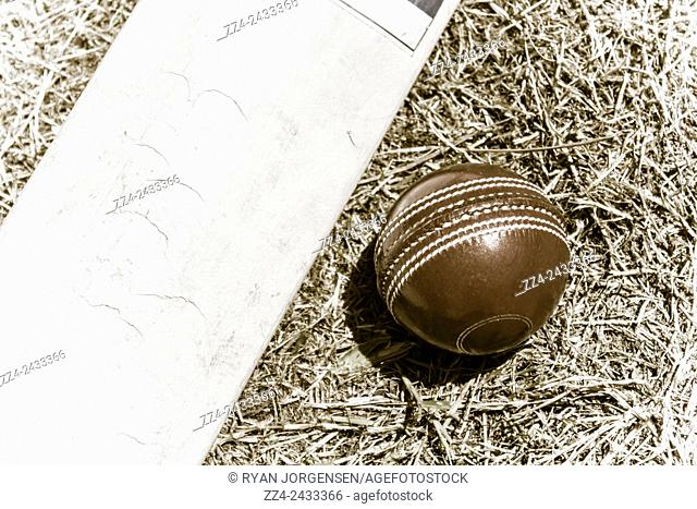 Old-fashioned still life picture on a cricket bat and ball on test ground playing pitch. Sport Nostalgia