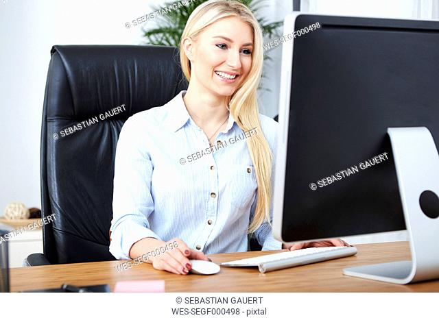Portrait of smiling blond woman working at desk