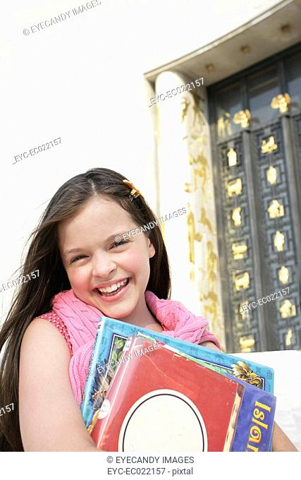 girl with school books smiling at camera