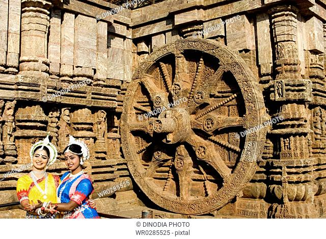 Odissi dancers strike pose re-enacts Indian myths such as Ramayana in front of iconic Sun Chariot in world heritage Sun temple complex in Konarak , Orissa