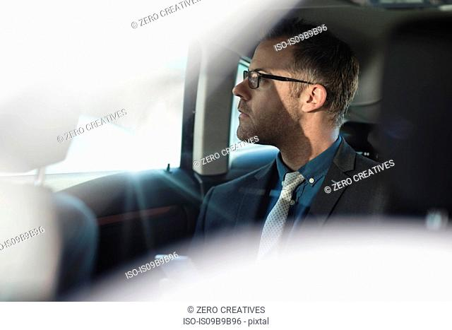 Businessman sitting in back of car, holding smartphone