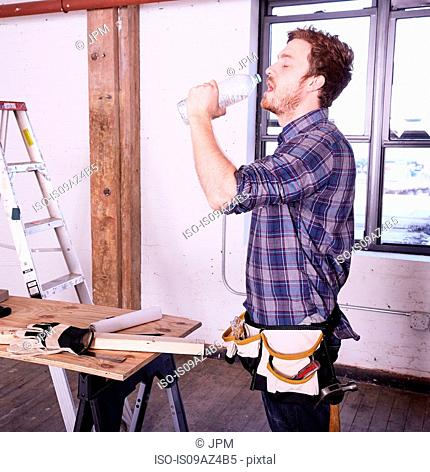 Carpenter in workshop drinking from water bottle