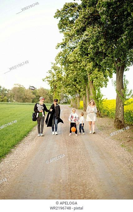 Family and friends walking on dirt road by oilseed rape field