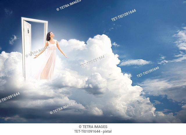 Young woman getting out from door in clouds