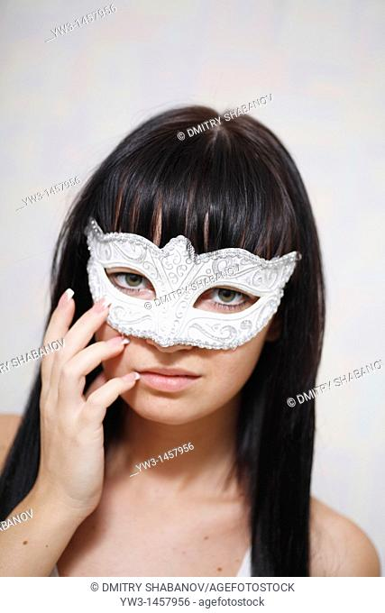 pretty brunette girl indoors weared in carnival mask