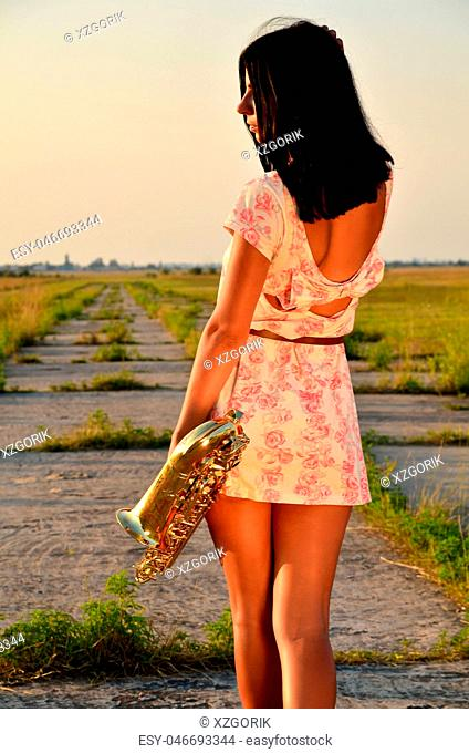 A young girl with a saxophone in his hands on the ground