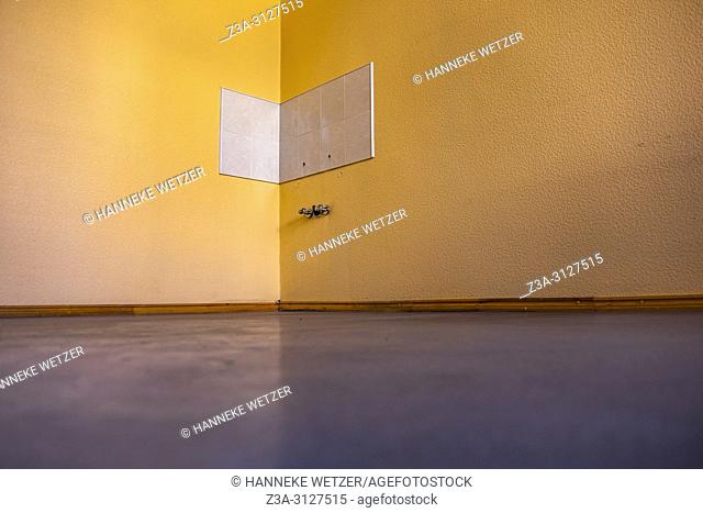 Blue floor with orange wall and missing sink in Riga, Latvia, Baltic States