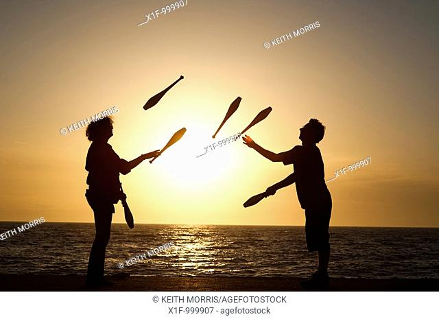 Two people juggling with clubs at sunset on Aberystwyth promenade wales UK