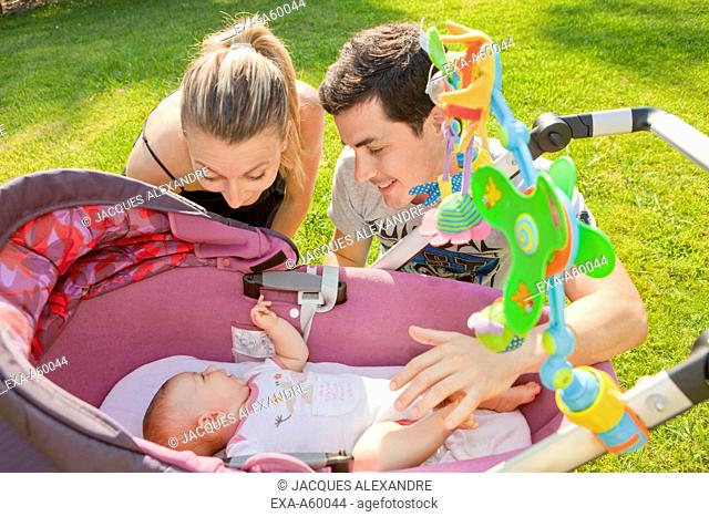 Father and mother playing with baby in baby carriage at park