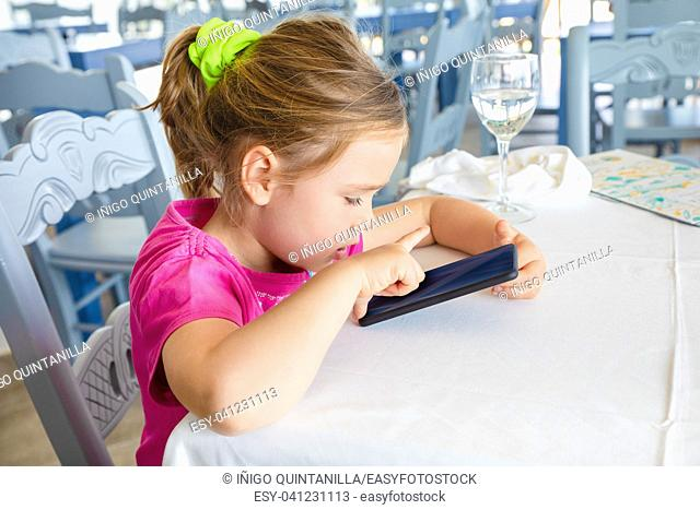 blonde caucasian girl four years old in summer, pink shirt, sitting in a restaurant watching and surfing internet with finger on smartphone or mobile phone