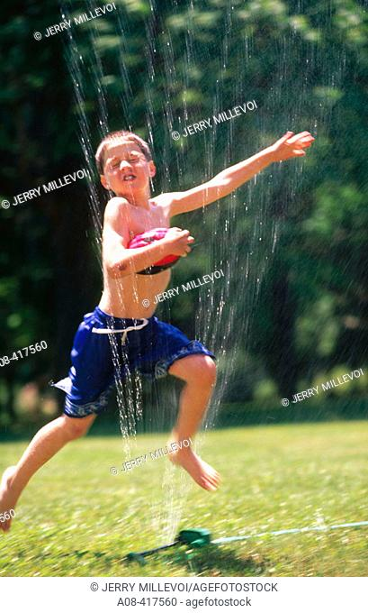 Boy runs through sprinkler with ball. Pennsylvania, USA