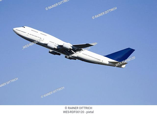 Aeroplane flying against blue sky, low angle view