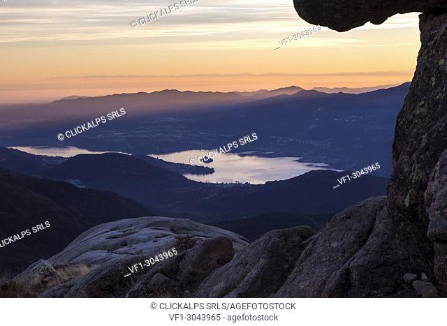 View of the Lago d'Orta and Isola di San Giulio from a group of rocks at the top of Mottarone. Stresa, Verbano Cusio Ossola, Piedmont, Italy