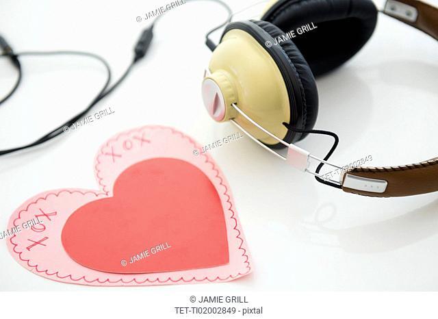 Studio shot of heart shaped paper cutout and headphones