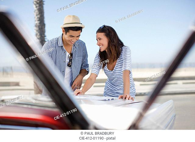 Smiling couple reading road map on convertible