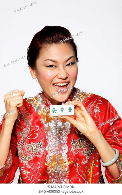 Happy woman wearing Chinese jacket and holding matching Mahjong tiles which mean Jack pot