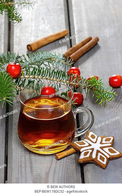Glass of hot tea among christmas decorations
