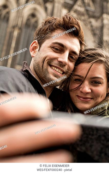 Germany, Cologne, young couple taking selfie in front of Cologne Cathedral