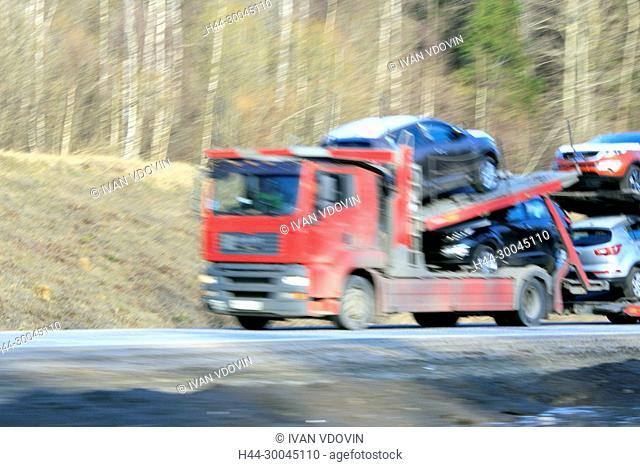 Delivery track car transporter speeding on a highway