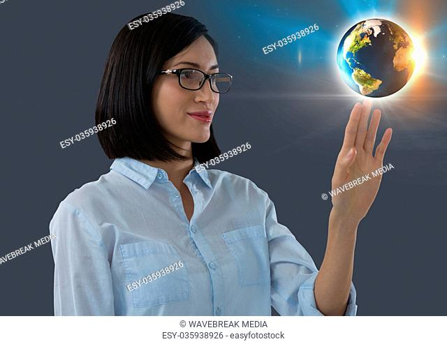 World globe and Businesswoman reaching touching air in front of plants on window