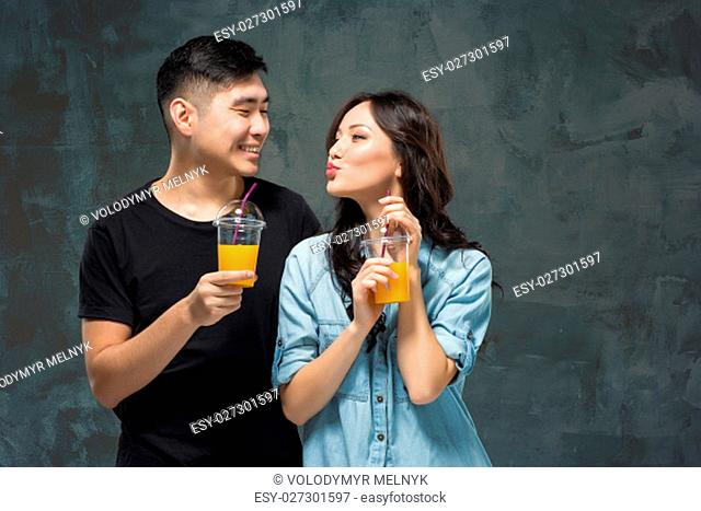 A young pretty Asian woman with a glass of orange juice in the hands at gray studio background