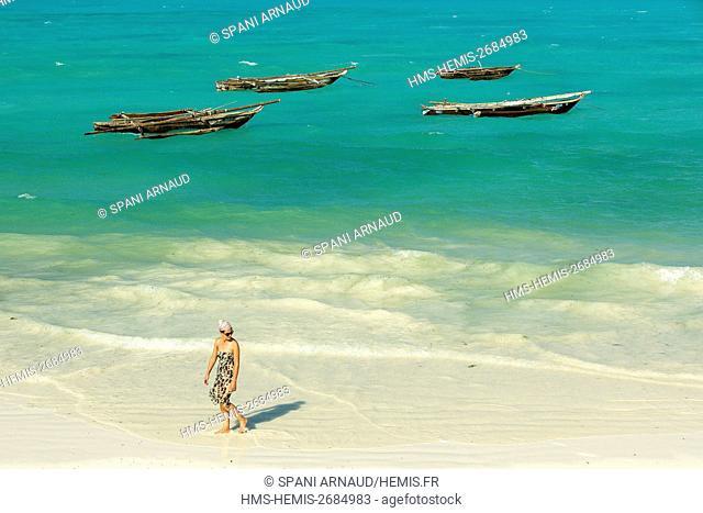 Tanzania, Zanzibar, Jambiani, young woman tourist walking on the beach