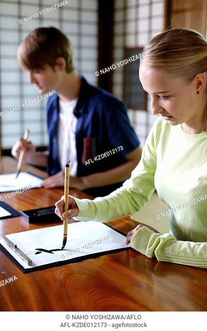 Caucasian couple practicing calligraphy at traditional Japanese house
