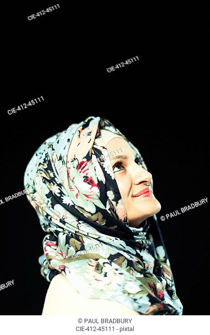 Portrait smiling, confident woman in floral hijab looking up