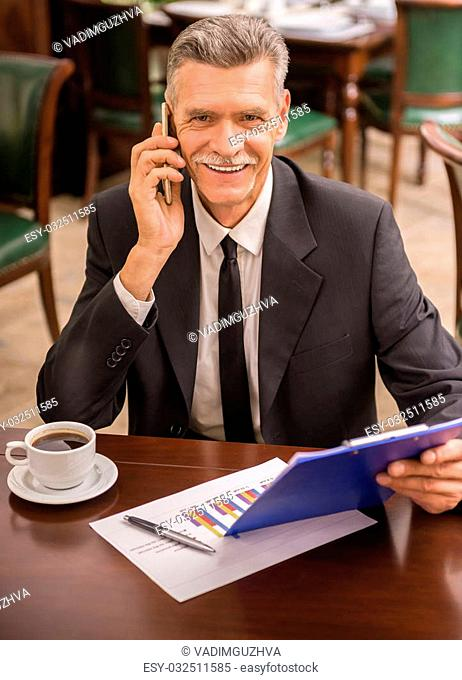 Senior businessman in suit sitting in cafe and reading document