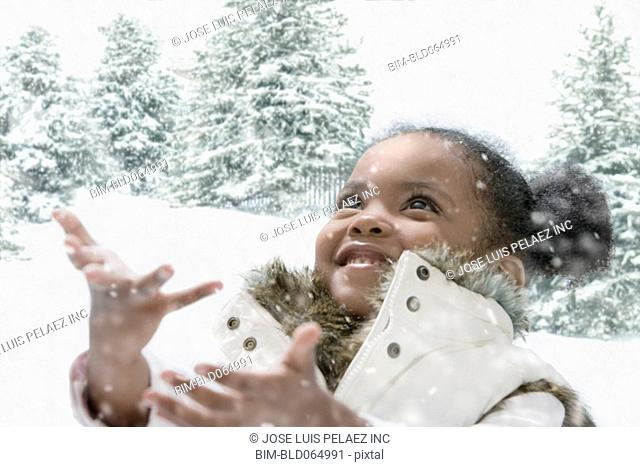African girl catching snowflakes