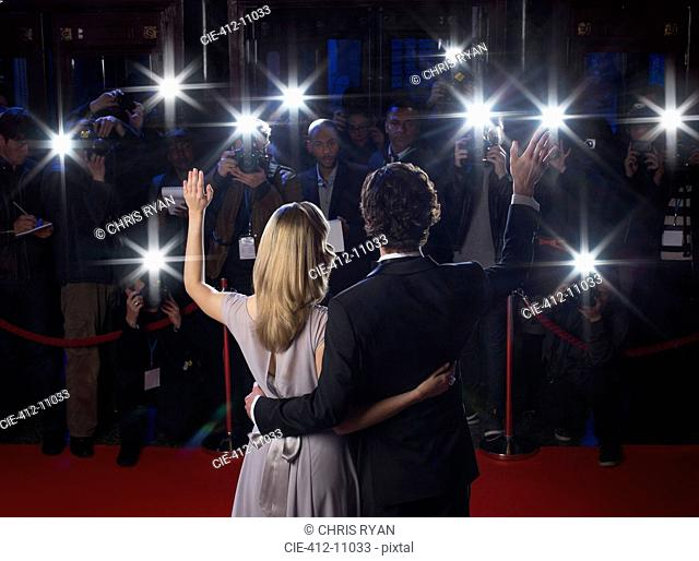 Rear view of celebrity couple waving to paparazzi at red carpet event