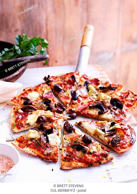 Capricciosa pizza on pizza peel, close-up
