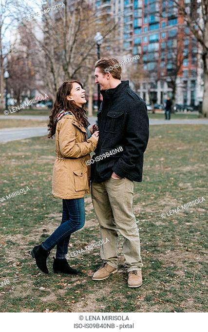 Young couple standing outdoors, face to face, laughing