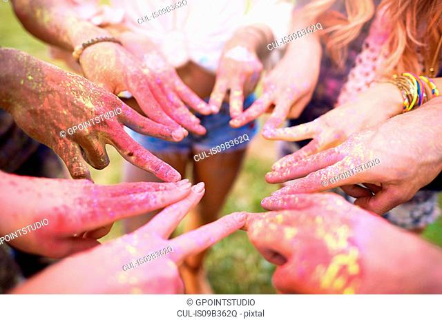 Group of friends at festival, covered in colourful powder paint, connecting fingers with peace signs, close-up