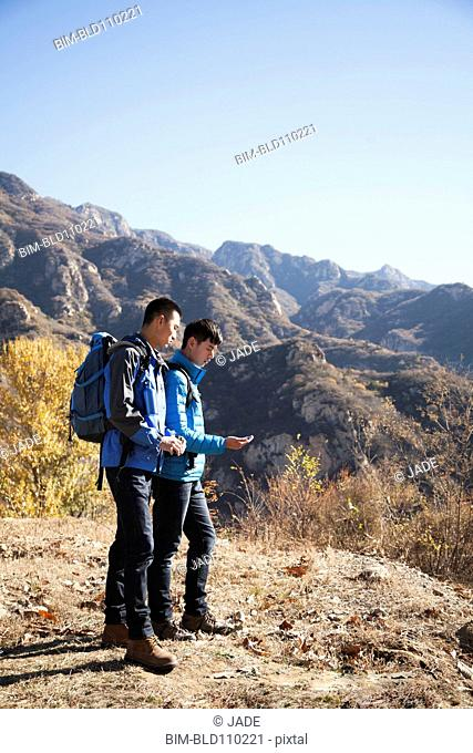 Chinese men hiking on rural hilltop