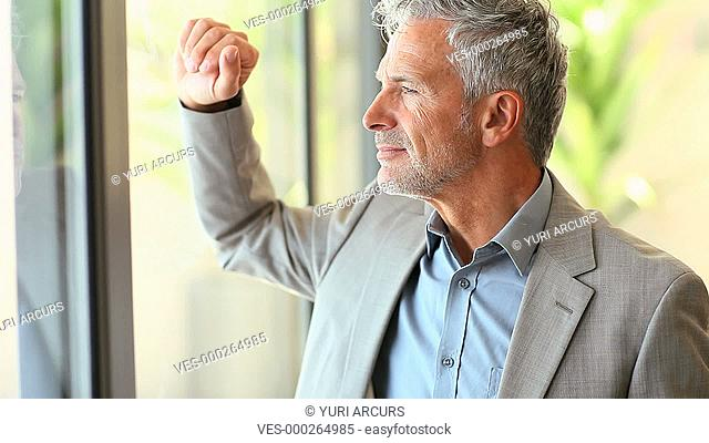 An attractive senior businessman sipping a cup of fresh coffee while looking out the window
