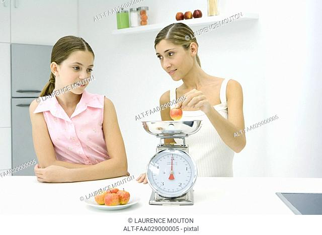 Woman and girl in kitchen, weighing apple