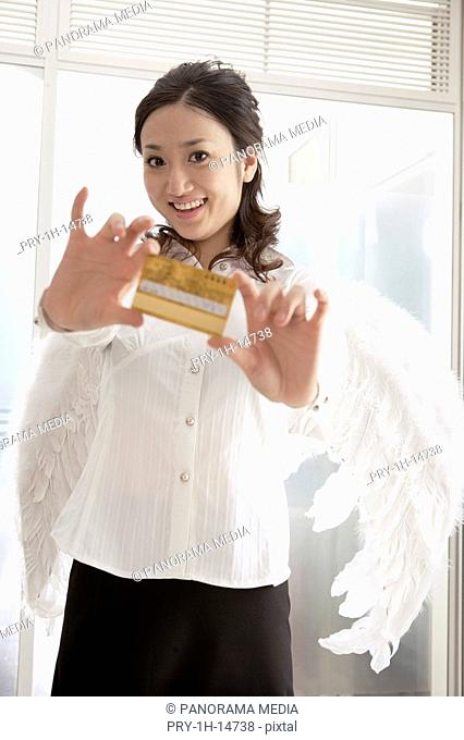 Portrait of a young woman wearing angel wings and holding credit card