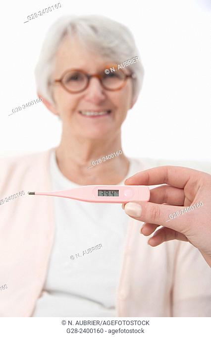 Young nurse or help or granddaughter holding a medical thermometer for patient or grandmother who is laughing in the background