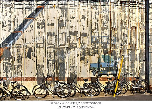 Bicycles parked at faded wall of crane service building in Nakaikegami, Tokyo, Japan