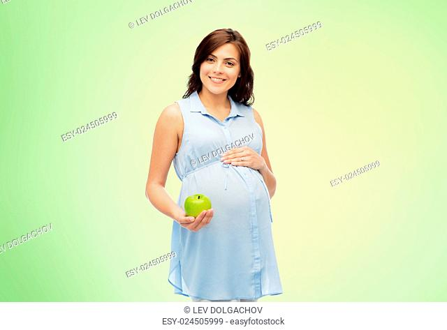 pregnancy, healthy eating, food and people concept - happy pregnant woman holding green apple over green natural background